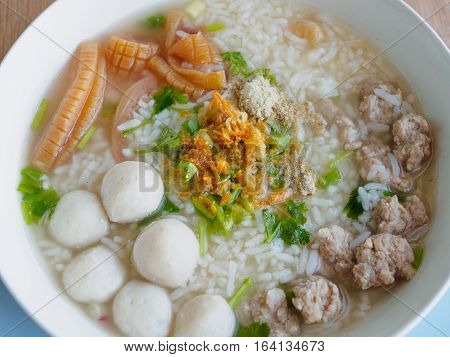 Rice porridge with shrimp, fish ball, pork, crispy squid, coriander, spring onion, pepper powder