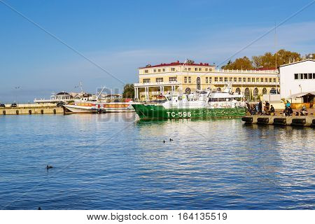 Sochi Russia - November 1 2015: Rescue and border guard motorboat moored at pier in Sochi seaport. Fishermen catch fish with fishing rods. Marine station complex Port. Krasnodarskiy kray Russia