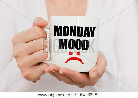 Monday mood with sad symbol on white coffee cup held by a woman