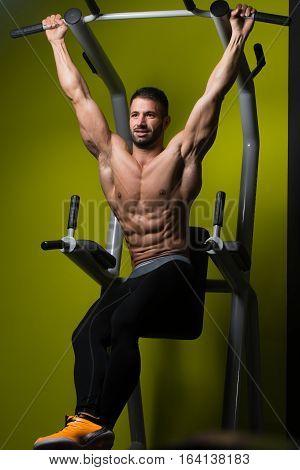 Muscular Man Performing Hanging Leg Raises Exercise