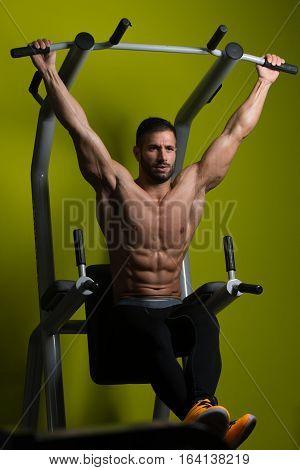 Healthy Man Performing Hanging Leg Raises Exercise