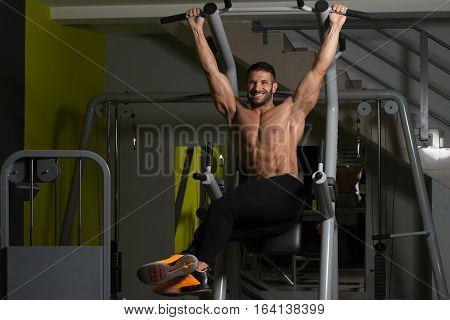 Young Man Performing Hanging Leg Raises Exercise