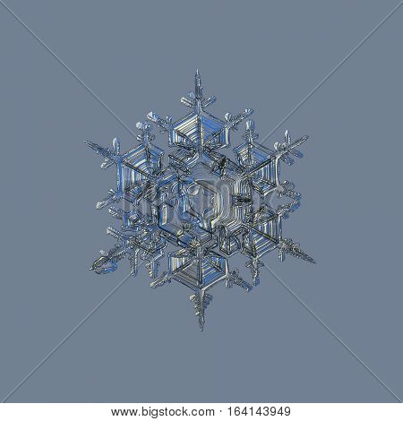 Snowflake isolated on uniform grey background. This is macro photo of real snow crystal: big split plate stellar dendrite with complex structure.