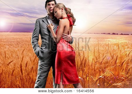 Portrait young beautiful couple under Golden wheat ready for harvest growing