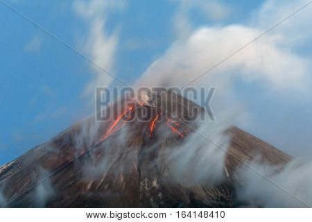 Volcanic landscape: active Klyuchevskoy Volcano view of top of a volcanic eruption - lava flows on of volcano; plume of gas steam and ashes from crater. Kamchatka Peninsula Russian Far East Klyuchevskaya Group of Volcanoes.