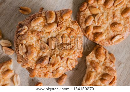 Salted crunchy peanut cookies freshly baked with crumbs and pieces on a wooden plate top down view