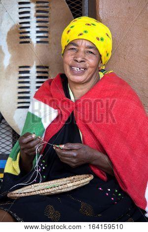 South Africa, Gauteng, Lesedi Cultural Village - 04 July, 2015. Beautiful African Zulu woman Bantu nation is weaving a beads jewelry. Traditional handmade costume headdress and blanket.