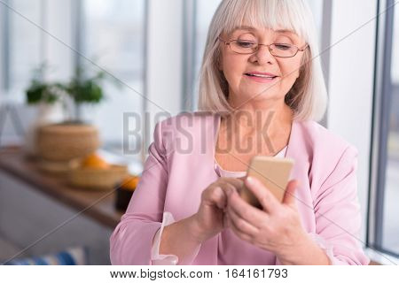 Whom should I call. Delighted bright elderly lady wanting to call someone while searching through her contacts list and wearing red spectacles
