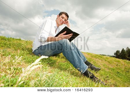 happy man reading a book sitting on green grass