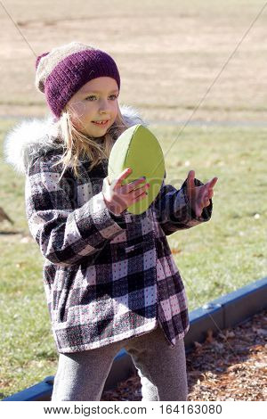 adorable school age girl holding football wearing coat