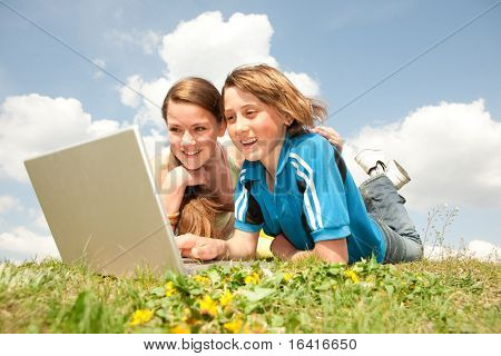 Two Smiling teenagers with laptop resting on meadow.