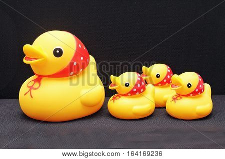 The composition of a toy duck and her ducklings on a black background.