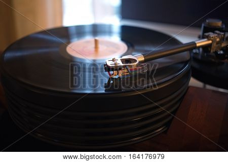 Vintage turntable rotating LP record in a room with subdued light. Horizontal view closeup