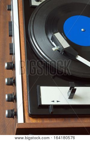 Old vintage vinyl record player in brown wooden case playing LP record with blue label. Top view vertical photo closeup