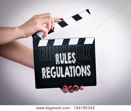 Rules And Regulations. Female hands holding movie clapper.