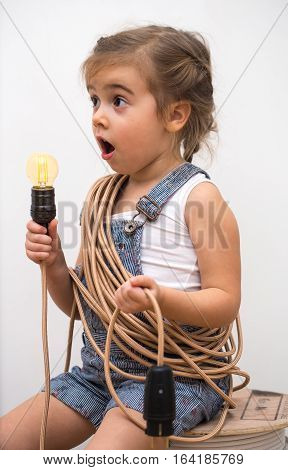 little cute girl with light bulb in hand sitting on the Hank of wires for electricians, concept ideas