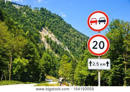 Roadside signs in the countryside. Indicate the speed limit and the prohibition of overtaking