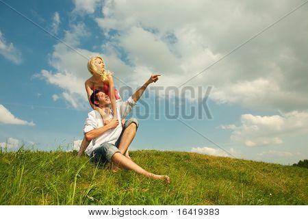 Amor de la joven pareja sonriendo bajo el cielo azul