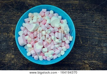 Colorful marshmallows in a bowl on an old rustic wooden table macro texture background with space for text. A pile of mini white pink and orange puffy marshmallows. Marshmallow concept. Copy space.