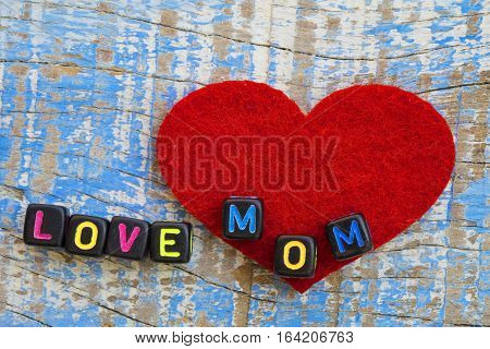 Word love mom on with dices on wooden background