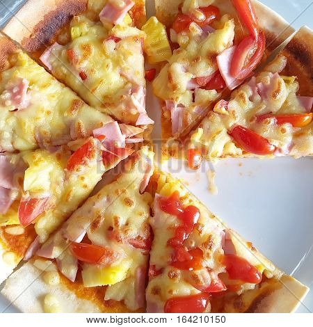 Home delivered Hawaiian pizza piece in a white dish with slices missing