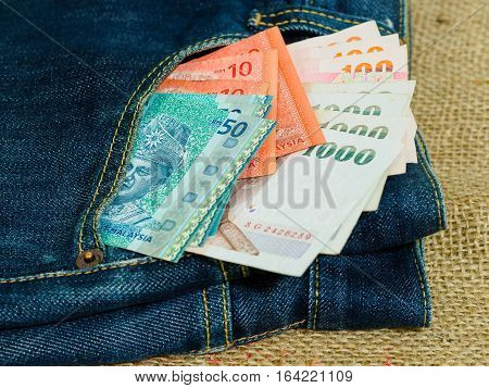 Blue jeans pocket with Malaysian and Thai banknotes on brown hemp sack texture background. Money for travel and shopping