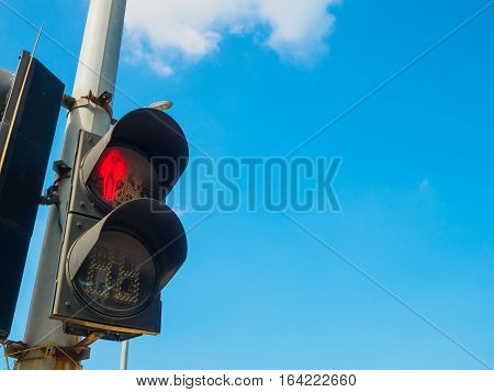 Traffic light shows red light for pedestrians with blue sky