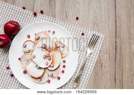Home made pancakes with cranberries and sugar powder on a white plate. Wooden table rustic decoration berries apples and a fork. Top view flat lay view from above