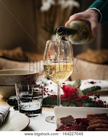 Man pours white wine into a glass