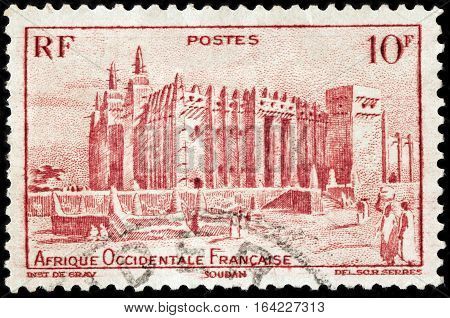 LUGA RUSSIA - NOVEMBER 29 2016: A stamp printed by FRENCH WEST AFRICA shows view of Great Mosque of Djenne. Mosque is located in the city of Djenne on flood plain of Bani River circa 1947