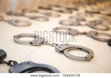 row of law enforcement silver metal handcuffs prepare for training on white table