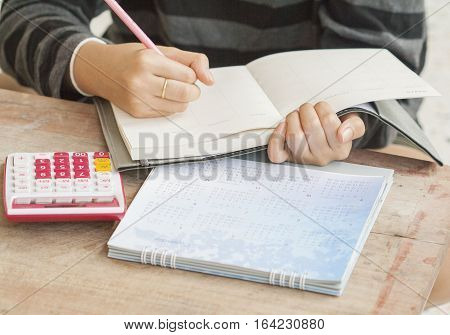 woman writing notebook monthly planner record for financial