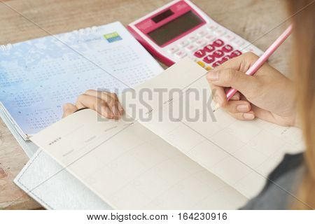 woman writing notebook monthly planner for financial on table