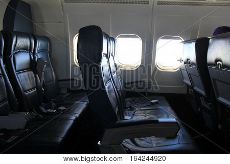 Image of interior of jet, with black leather seats, empty and ready for customers to board and seat for flight.