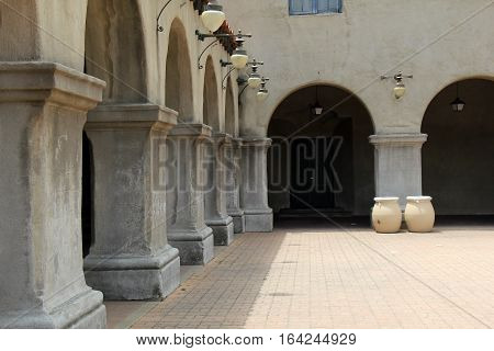 Gorgeous architecture of building, with heavy stone columns and brick courtyard.