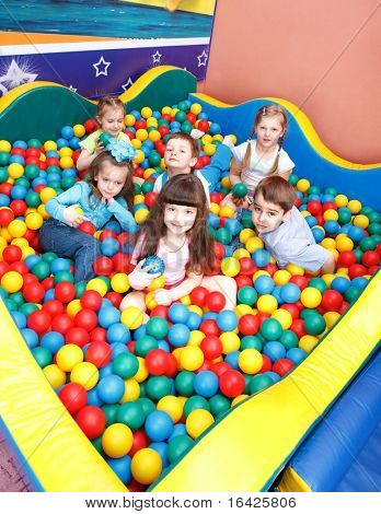 Joyful preschool kids playing in the colorful balls