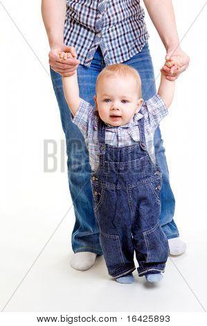 Süßes Baby, erste unsicher Schritte, unterstützt von Mama