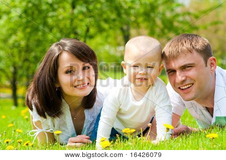 Mother, father and baby lying on grass