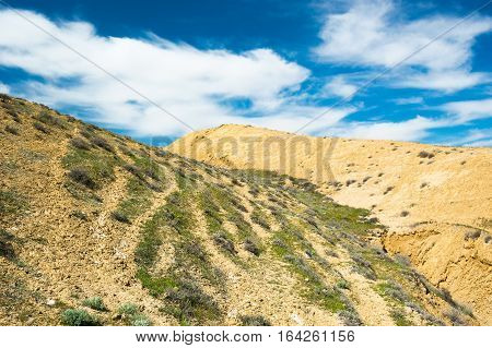 Clay mountains landscape with beautiful cloudy sky. Steppe vegetation
