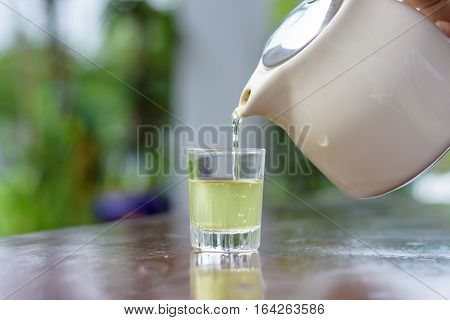 Tea pot pouring hot green tea in glass
