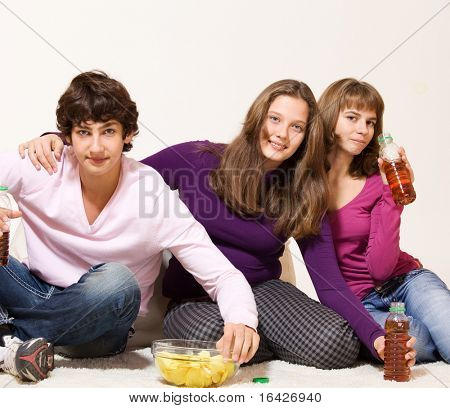 Hungry friends with crisps and drinks in bottles