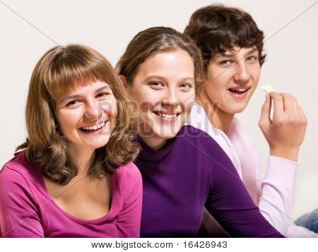 Three teenage friends, smiling, with crisps in hand