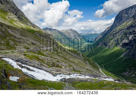 Trollstigen serpentine road down to canyon valley and mountain river. National travel route of Norway.
