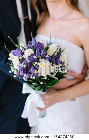 Newlyweds and wedding bouquet. The loving newlyweds. Groom and bride outdoors. Beautiful wedding bouquet in hands of the groom and bride.
