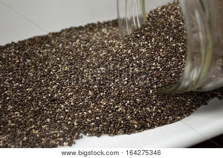 Chia Seeds Spilling Out Of Container, Close Up