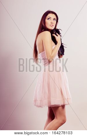 Beauty fashion and elegant people concept - young brunette slim woman in bright strapless dress holds clutch bag