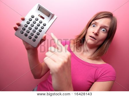 Broke - Portrait of a young woman holding a calculator, pointing at it with her finger and looking really alarmed