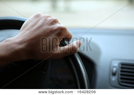 Driving - young man's hand holding the steering wheel