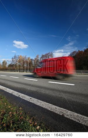 Speeding concept - Red van moving fast (speeding) on a highway