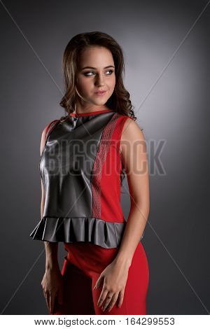 Gorgeous brunette woman wearing trendy evening clothes  posing to camera over dark background at studio, copy space